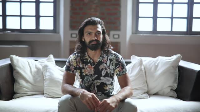 vidéos et rushes de verticale de mouvement lent de jeune homme s'asseyant sur le sofa dans le grenier moderne - loft