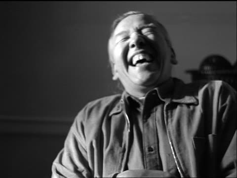 vídeos de stock e filmes b-roll de b/w slow motion portrait seated middle-aged hispanic man laughing indoors - só homens maduros