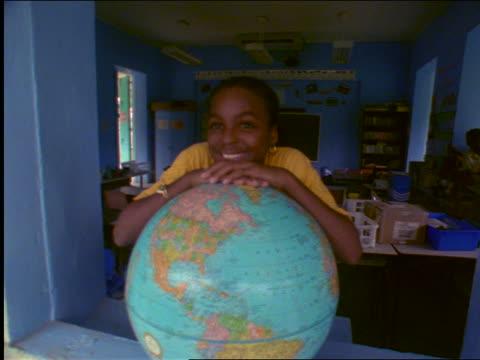 slow motion portrait smiling black girl leaning on globe in school window / st. john, virgin islands - st. john virgin islands stock videos & royalty-free footage