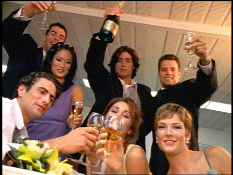 slow motion PORTRAIT wedding party with champagne glasses raised in bowling alley snack bar