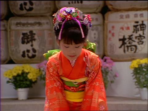 vídeos de stock e filmes b-roll de slow motion portrait young japanese girl in kimono bowing to camera / sake casks in background / japan - respect