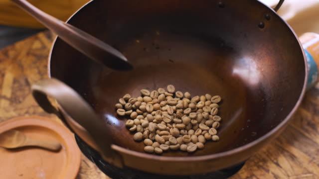 vídeos de stock, filmes e b-roll de o movimento lento do uc derrama o feijão de café fresco na colher de madeira da bandeja do metal e no feijão de café fresco roasted com colher de madeira na bandeja que prepara para fazer o café caseiro - bean