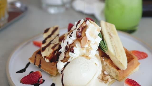 vídeos y material grabado en eventos de stock de cámara lenta vierte miel en postre de helado de crepes en mesa - waffles