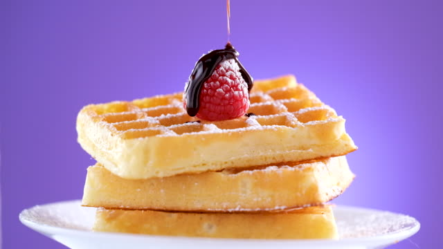 slow motion pouring chocolate sauce on to waffles - syrup stock videos & royalty-free footage