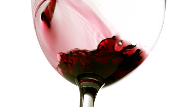 Slow motion pouring red wine on white background from below