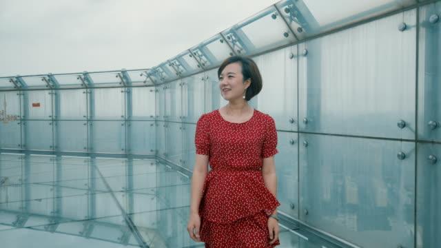 slow motion pretty woman wlking on glass skywalk spans - 美しい人点の映像素材/bロール