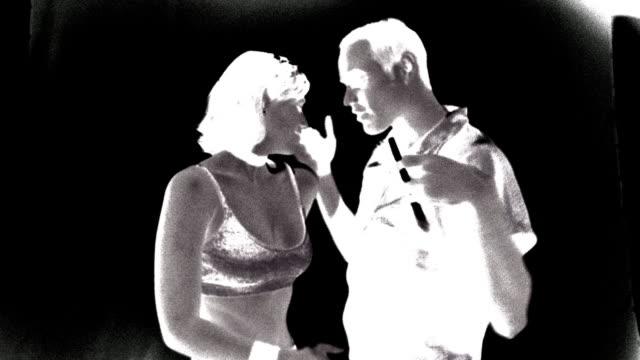 B/W NEGATIVE slow motion MS PROFILE couple dancing / flashing lights