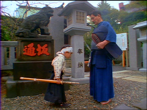 slow motion profile japanese man + small boy with kendo gear bowing to each other / japan - respect点の映像素材/bロール