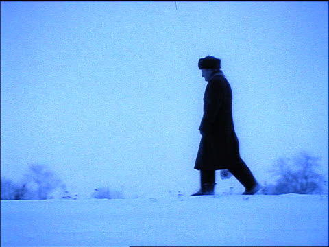 BLUE slow motion PAN profile of man walking in snow / Russia