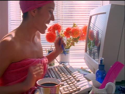 stockvideo's en b-roll-footage met slow motion profile woman in pink towel sitting at computer typing + smiling / drinks coffee - in een handdoek gewikkeld