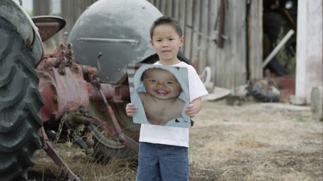 slow motion push of boy holding up photo of himself as baby with scar on chest. - korta ärmar bildbanksvideor och videomaterial från bakom kulisserna