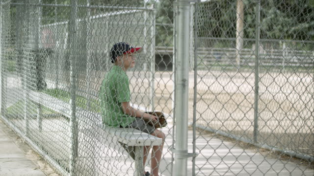 slow motion push of boy sitting in dugout behind chain link fence. - dugout stock videos & royalty-free footage