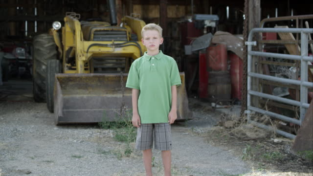 slow motion push of boy with cleft lip standing in front of tractor. - zoom in stock videos & royalty-free footage