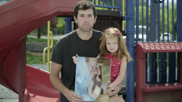 vidéos et rushes de slow motion push of father and daughter holding picture of her while in hospital. - toboggan