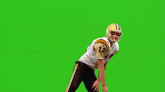 chroma key slow motion quarterback throwing football, raising arms + jumping in air in victory / green background - american football player stock videos & royalty-free footage