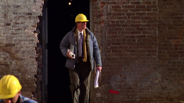 slow motion rack focus architect in hard hat carrying blueprints exiting doorway on construction site