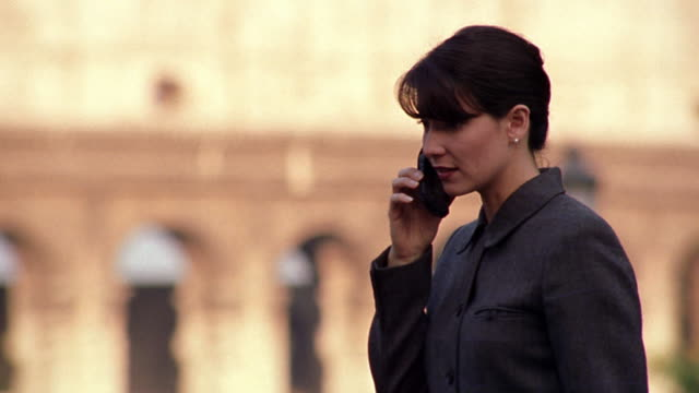 slow motion rack focus pan businesswoman on cellular phone pacing with colosseum in background / rome, italy - yuppie stock videos and b-roll footage