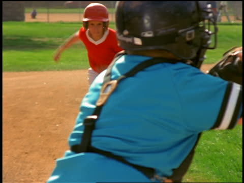 slow motion rack focus from close up catcher in foreground to another boy running + sliding into home plate - baseballspieler stock-videos und b-roll-filmmaterial