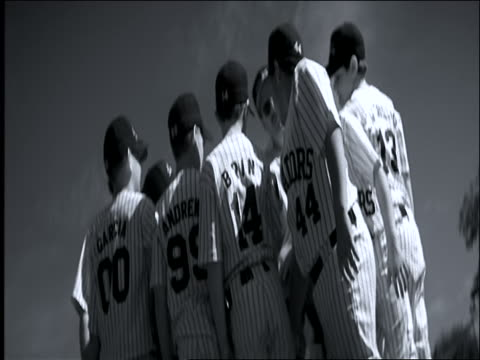 B/W slow motion rack focus Little League baseball players in huddle with coaches / raise hands together