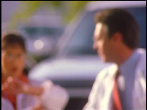 vidéos et rushes de slow motion rack focus male doctor + female doctor talking + walking briskly outdoors - parking