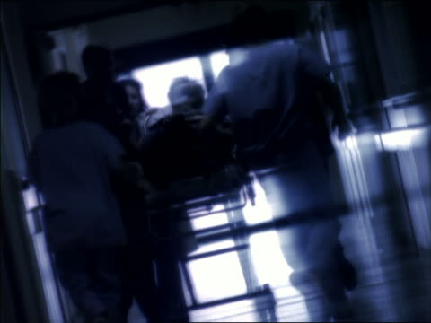 stockvideo's en b-roll-footage met slow motion rack focus medium shot emts and medical personnel pushing patient on gurney down hallway with tilt down to running feet - ziekenhuisbed
