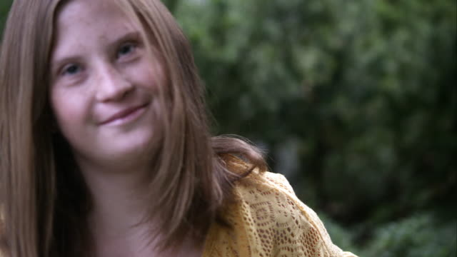 Slow motion rack focus of girl with down syndrome smiling.