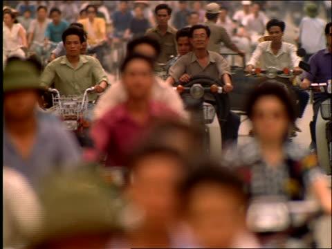 vídeos de stock, filmes e b-roll de slow motion rack focus of men on mopeds in traffic / vietnam - ocidentalização