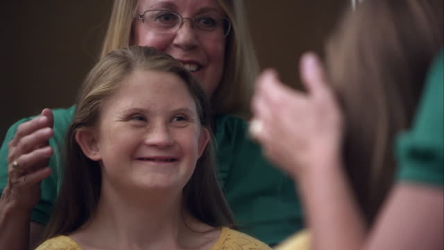 slow motion rack focus of mother brushing hair of daughter with down syndrome. - persons with disabilities stock videos & royalty-free footage