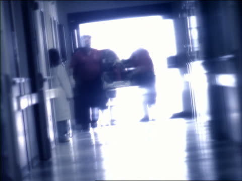 slow motion rack focus wide shot emts and medical personnel pushing patient on gurney through er doors + down hallway - blurred motion stock videos & royalty-free footage