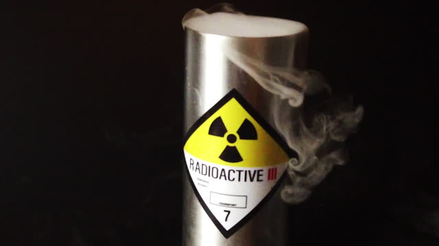 slow motion radioactive canister with smoke billowing out panning - weapons of mass destruction stock videos & royalty-free footage
