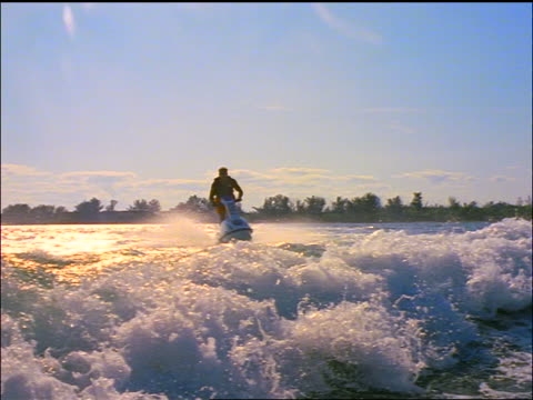 slow motion rear boat point of view pan man riding jet boat jumping over wake from boat - acquascooter video stock e b–roll