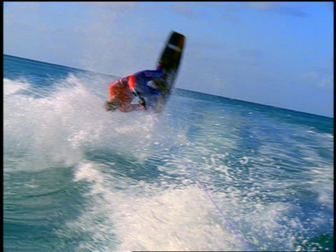 slow motion rear boat point of view man riding wakeboard flipping + raising arm in victory - cinematography stock videos & royalty-free footage