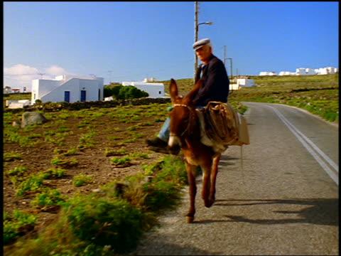 vídeos y material grabado en eventos de stock de slow motion rear car point of view senior man riding mule on country road toward camera / santorini, greece - burro