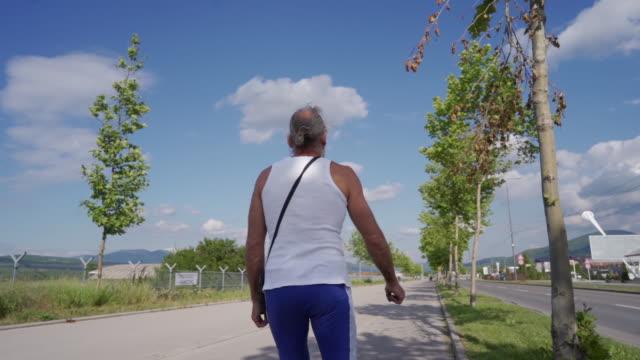 vídeos de stock, filmes e b-roll de imagens traseiras em câmera lenta de um homem sênior patinando na linha - só um homem idoso