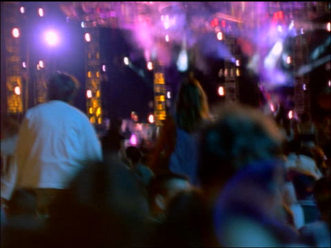 slow motion rear view audience + stage with colored lights at rock concert (garth brooks) / central park - 1998 stock-videos und b-roll-filmmaterial