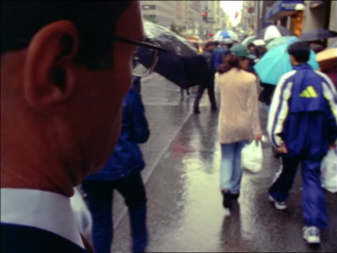 slow motion rear view close up over-the-shoulder businessman standing on sidewalk checking watch as time lapse people walk past him - 腕時計点の映像素材/bロール