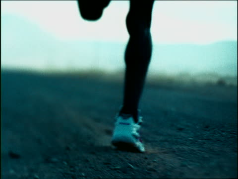 overexposed slow motion rear view close up tracking shot black male athlete's legs running in dirt / africa - スポーツシューズ点の映像素材/bロール