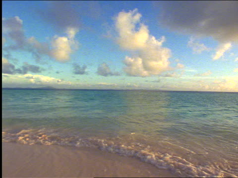vidéos et rushes de slow motion rear view couple with swimsuits running + diving into ocean surf / virgin gorda - 1999