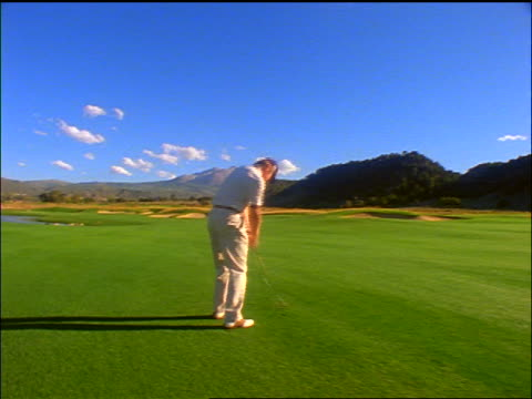 slow motion rear view dolly shot toward + past man hitting golf ball on fairway / mountains in background / colorado - maglietta polo video stock e b–roll