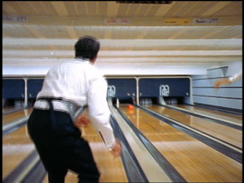 slow motion rear view pan group of men wearing tuxedos bowling in bowling alley + giving high fives - high five stock videos & royalty-free footage