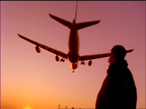 vídeos de stock, filmes e b-roll de slow motion rear view low angle silhouette tilt down man watching as airliner comes in for landing from above at sunset - 1990