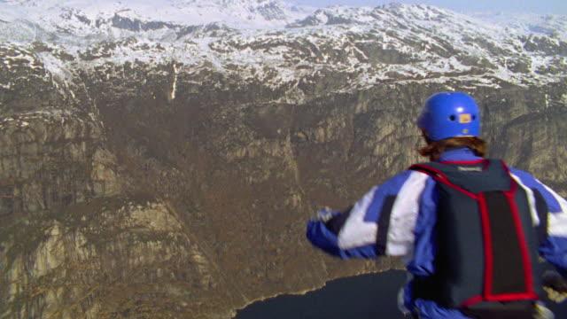 slow motion REAR VIEW man base jumping off cliff + flipping in air / Kjerag rock, near Stavanger, Norway