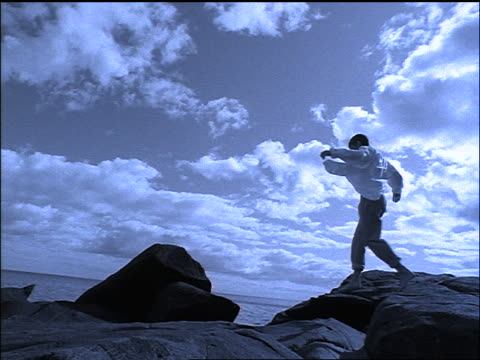 blue slow motion rear view man jumps from one boulder to another / looks out at ocean - manipolazione di colore video stock e b–roll