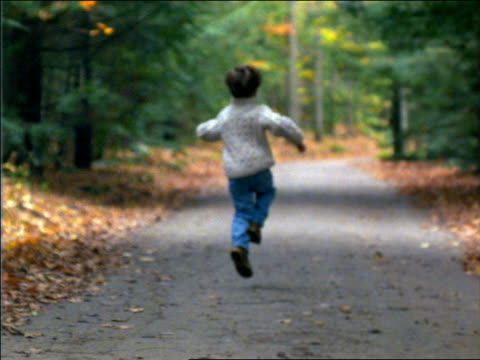 slow motion rear view of boy skipping down country road in Autumn / Connecticut