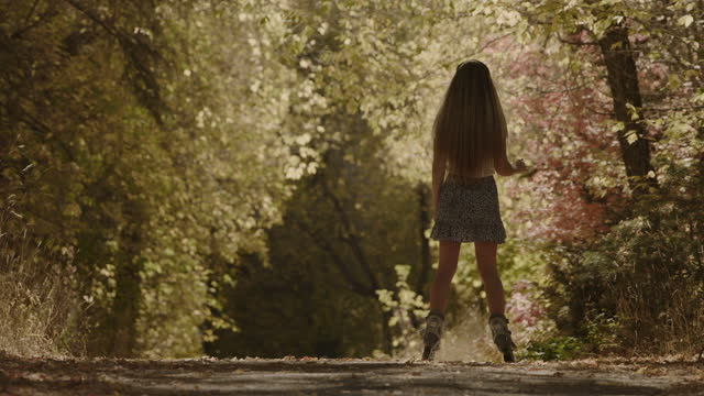 slow motion rear view of girl gliding on inline skates in park in autumn / american fork canyon, utah, united states - american fork canyon stock videos & royalty-free footage