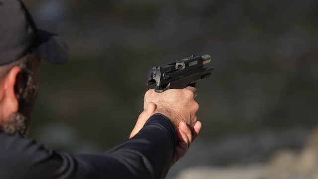 slow motion rear view of man shooting a hand gun outdoors, close-up. - one man only stock videos & royalty-free footage