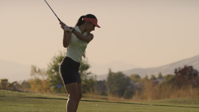 slow motion rear view of woman golfing / cedar hills, utah, united states - golf swing women stock videos & royalty-free footage