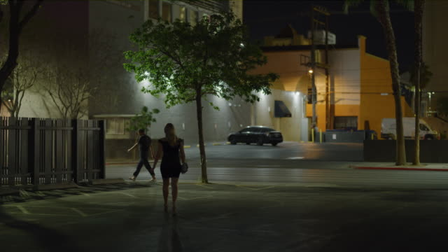 vídeos de stock, filmes e b-roll de slow motion rear view of woman prostitute walking toward man in city at night / las vegas, nevada, united states - prostituta