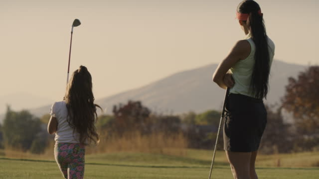 slow motion rear view of woman watching girl golfing then high-fiving her / cedar hills, utah, united states - sportbegriff stock-videos und b-roll-filmmaterial