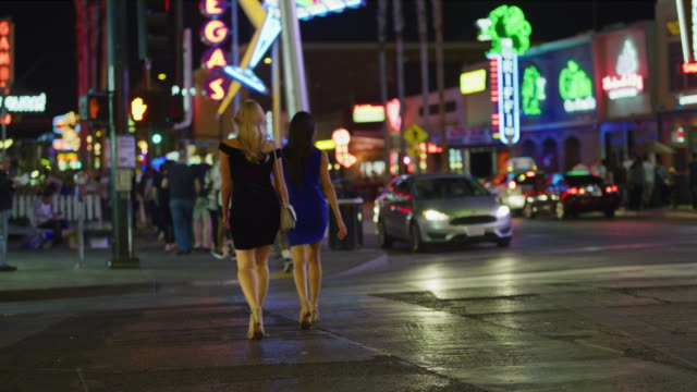 slow motion rear view of women crossing street in city at night / las vegas, nevada, united states - las vegas crosses stock-videos und b-roll-filmmaterial